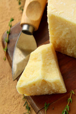 Parmesan cheese on a wooden table with knife  photo