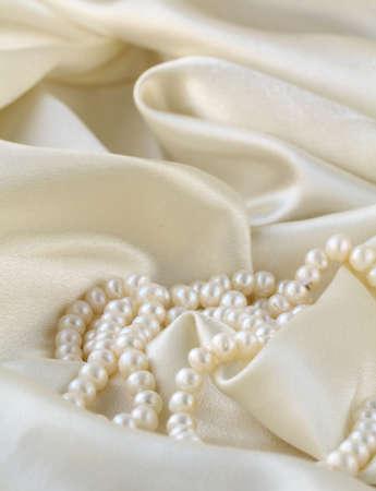 perlas: Las perlas de un collar en una tela de seda Foto de archivo