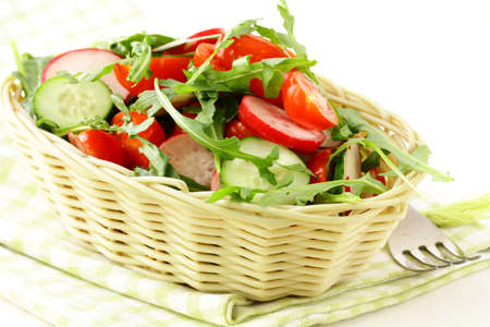 salad with arugula and cherry tomatoes on a wooden plate photo