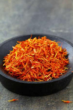 intense flavor: saffron treads in pile, on black wooden board