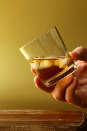 glass of scotch whiskey and ice in hand  photo
