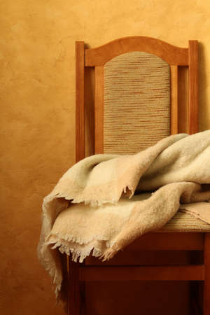 draped: chair with a blanket on a brown background
