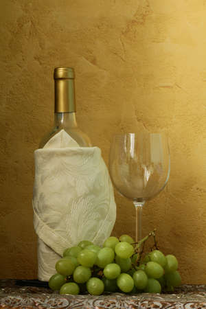 still life of wine bottles, glass and green grapes for vintage table photo