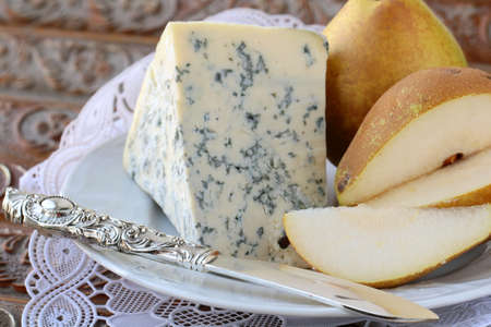 Blue cheese and pears on a vintage background photo
