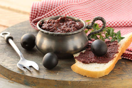 appetizer of olives, tapenade on a wooden board photo