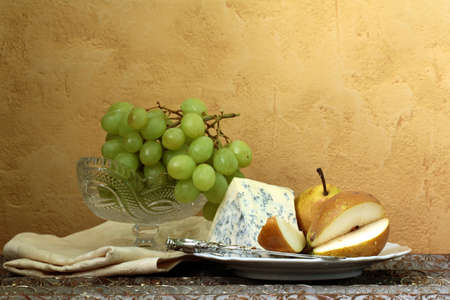 still life  blue cheese, green grapes and pears on the table, vintage photo