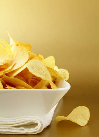 potato chips in a white bowl on a gold background Stock Photo - 12522717