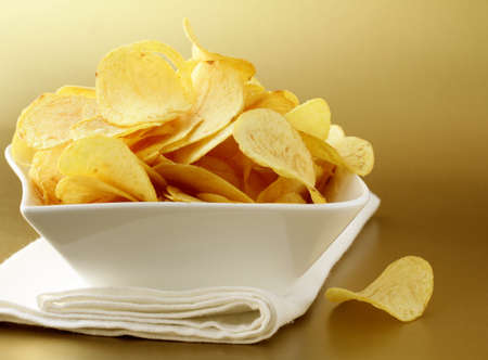 potato chips in a white bowl on a gold background Stock Photo - 12522781