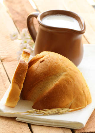 Ceramic jug with milk and a loaf of bread on a wooden table , rustic style photo