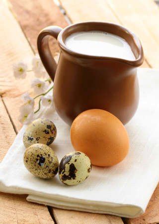 Ceramic jug with milk and eggs on a wooden table , rustic style photo