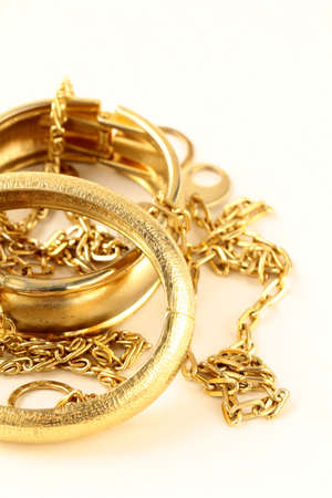 gold jewelry, bracelets and chains on a white background photo