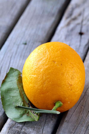 ascorbic: lemon yellow with a leaf on a wooden table Stock Photo