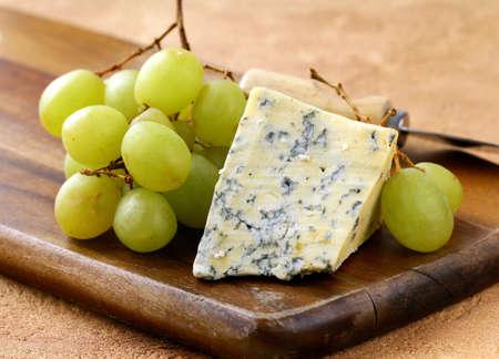 queso blanco: queso azul y uvas blancas en un tablero de madera Foto de archivo