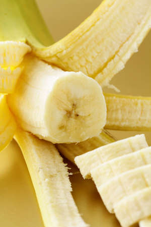 ripe banana cut into slices on a gold background photo