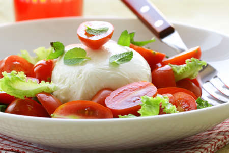 Traditional Italian Caprese Salad mozzarella with tomatoes and basil photo