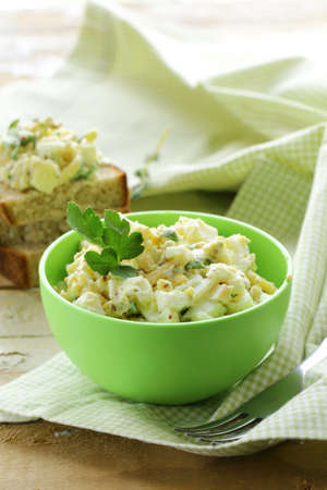 egg salad in a green cup with black bread photo