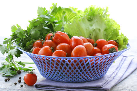 Cherry tomatoes and herbs in a wicker basket photo
