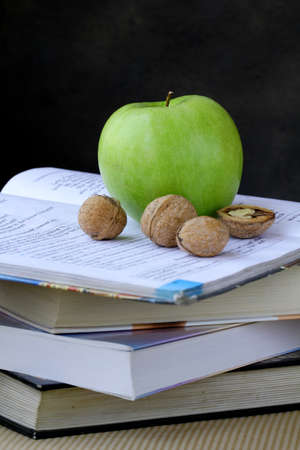 green apple and walnuts on a pile of books photo