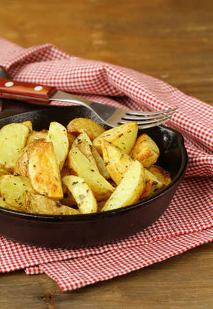 fresh potatoes fried in a pan on a wooden table  photo