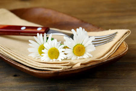 wooden plate and daisy on wooden background Stock Photo - 13880637