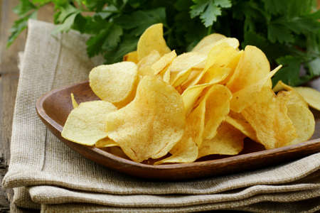 potato chips in wooden plate , on a wooden table Stock Photo - 13880638