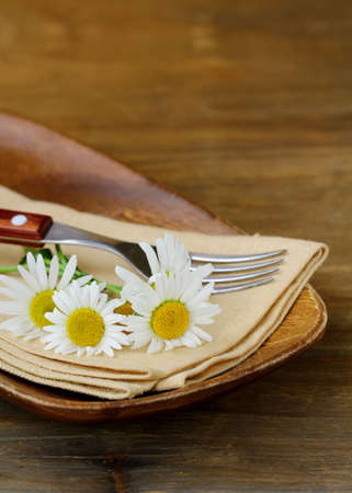 wooden plate and daisy on wooden background photo