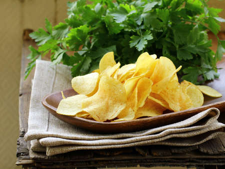 potato chips in wooden plate , on a wooden table  Stock Photo - 13898093
