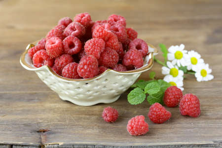 juicy ripe raspberries with mint leaves in a cup photo
