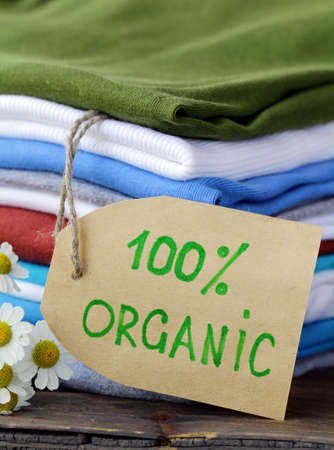 stack of colorful clothing with organic label and flowers photo