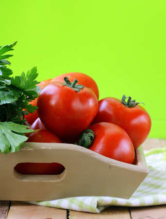 fresh red ripe tomatoes and parsley in a wooden bowl photo