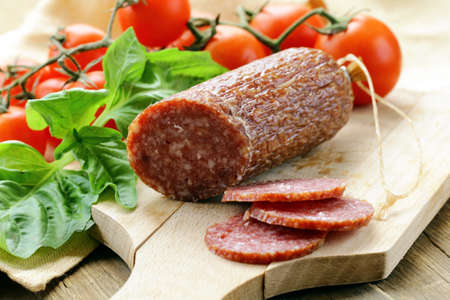 smoked: sliced meat sausage salami on wooden board with  green herbs