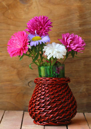 bouquet of autumn flowers in basket vase photo