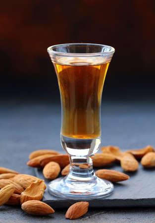 amaretto: Almond liquor amaretto with whole nuts on a dark background Stock Photo