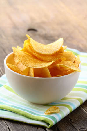 potato chips in a white bowl on a wooden table Stock Photo - 15424376
