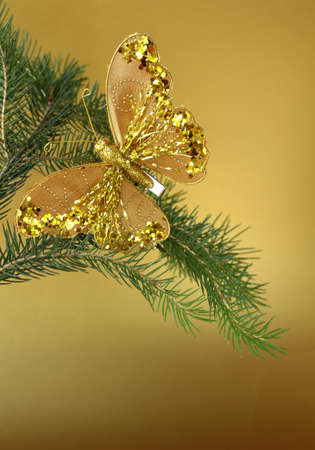Christmas decoration (golden butterfly) on the branches of fir photo