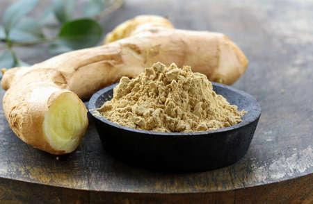 gemalen gember (specerijen) en vers op een houten plank Stockfoto