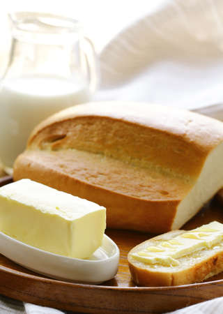 high calorie: butter,  loaf of white bread and milk on wooden plate