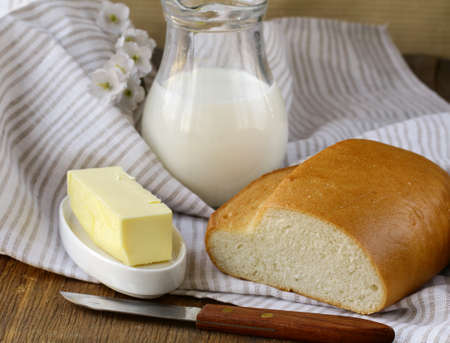 butter,  loaf of white bread and milk on wooden plate photo