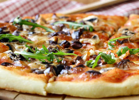 slice of pizza: Italian pizza with mushrooms and olives on a wooden board