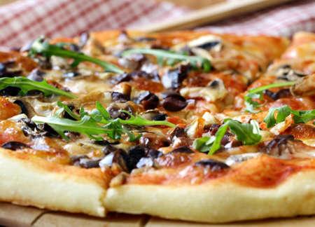 italienisches essen: Italienische Pizza mit Champignons und Oliven auf einem Holzbrett Lizenzfreie Bilder
