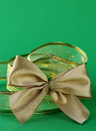 gold bow and ribbon  on a green background  photo