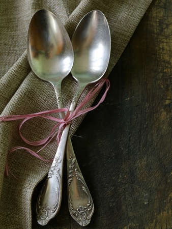 antique dishes: vintage silver cutlery on a wooden background