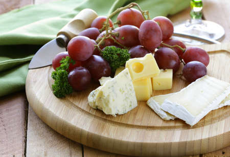 cheeseboard: cheeseboard with three kinds of cheese and grapes Stock Photo