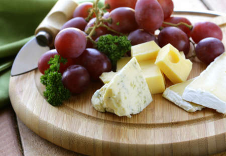cheese platter: cheeseboard with three kinds of cheese and grapes Stock Photo