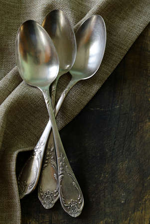 vintage silver cutlery on a wooden background photo