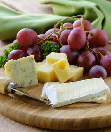 cheeseboard with three kinds of cheese and grapes Stock Photo
