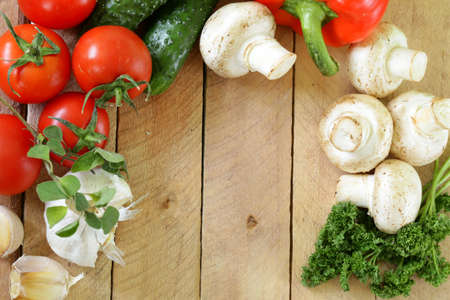 frame of vegetables (cucumber, tomato,mushrooms, garlic)  on a wooden background Stock Photo - 17438013