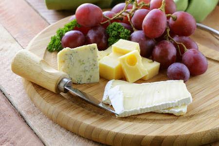 tabla de quesos: tabla de quesos con tres tipos de queso y uvas Foto de archivo