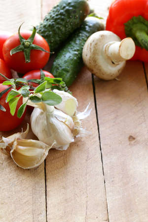 frame of vegetables (cucumber, tomato,mushrooms, garlic)  on a wooden background Stock Photo - 17505361