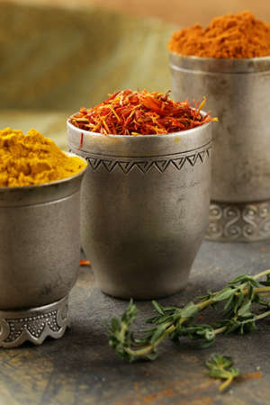 various spices (curcuma, paprika, saffron, coriander) in metal bowls photo